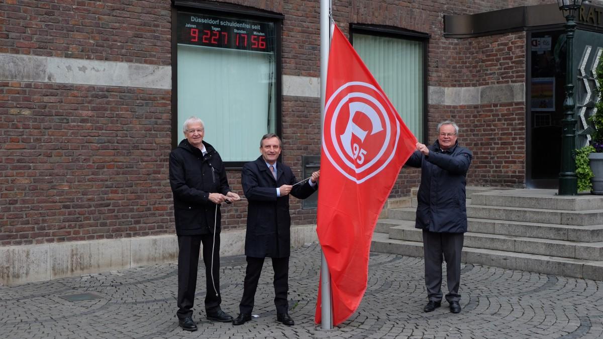 OB Geisel (Mitte), Bürgermeister Karen-Jungen (l.) Und F95-Vorstand Jäger Hissen Die Fortuna-Flagge Am Rathaus (Foto: Landeshauptstadt Düsseldorf/Michael Gstettenbauer)