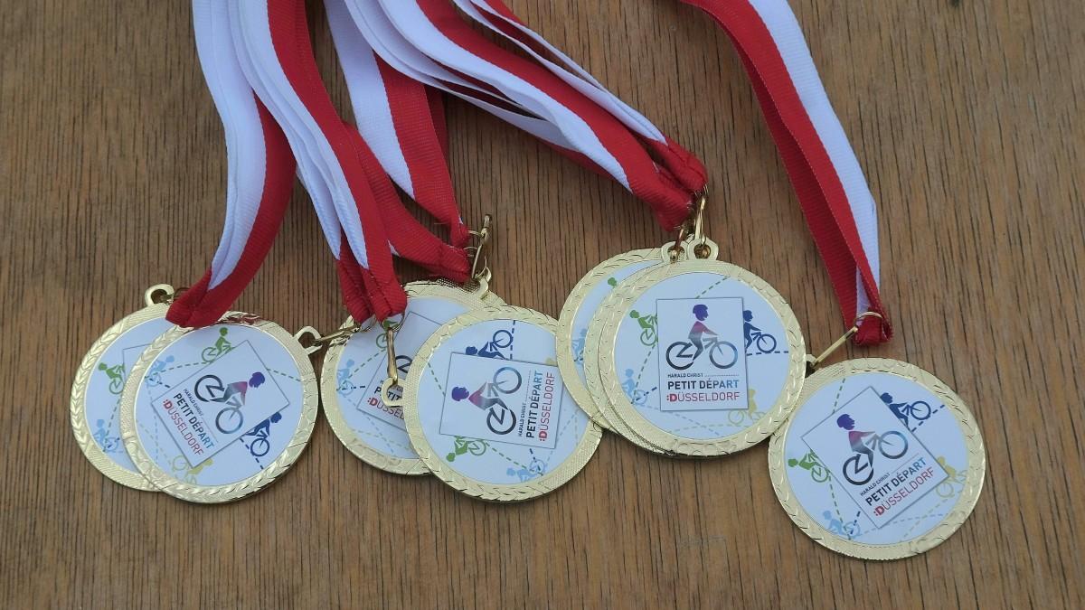 Mit Diesen Medaillen Werden Die Teilnehmenden Am Kinderradwettbewerb Petit Départ Ausgezeichnet (Foto: Landeshauptstadt Düsseldorf)